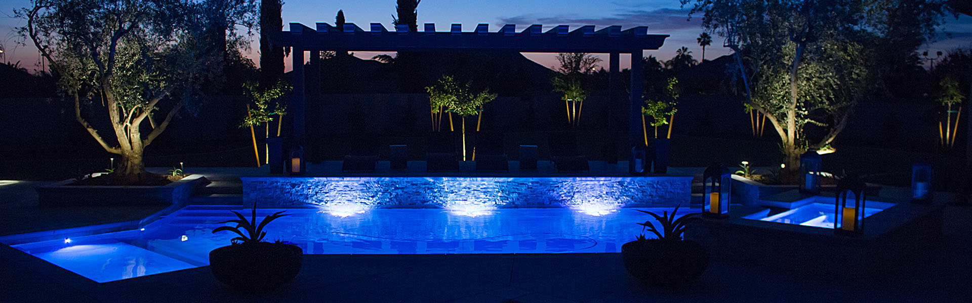 Swimming pool at night with blue underwater lights.