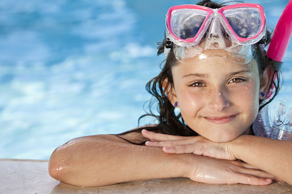 A happy young girl relaxing on the side of a swimming pool wearing pink goggles and snorkel