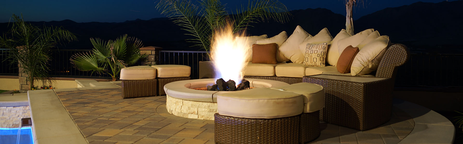 Lounge area with beautiful fire pit by the pool at night.