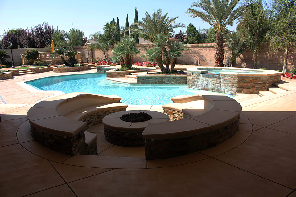 Fire pit with built in seating next to a stunning swimming pool.
