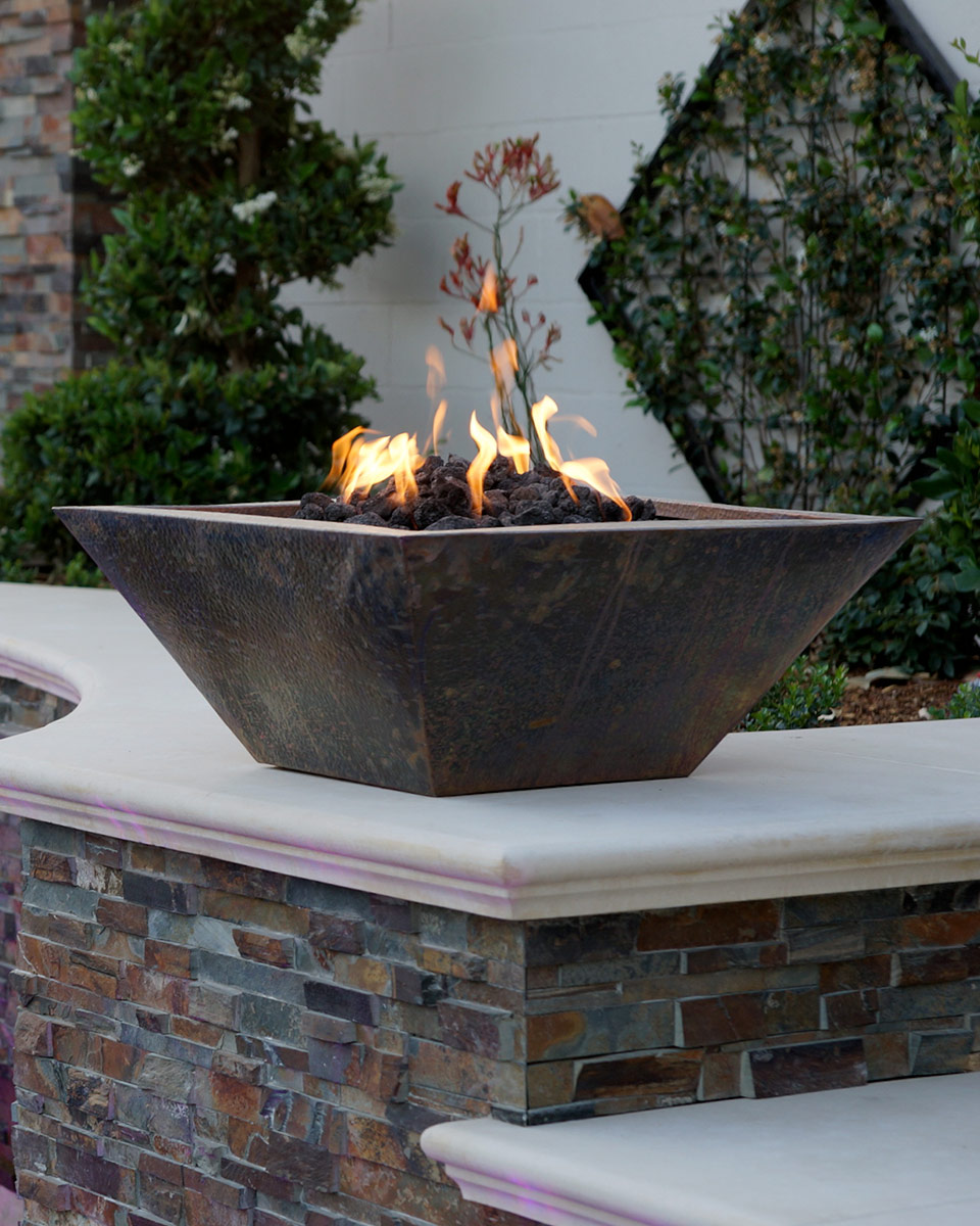 Fire bowl with flames next to a Bakersfield swimming pool.