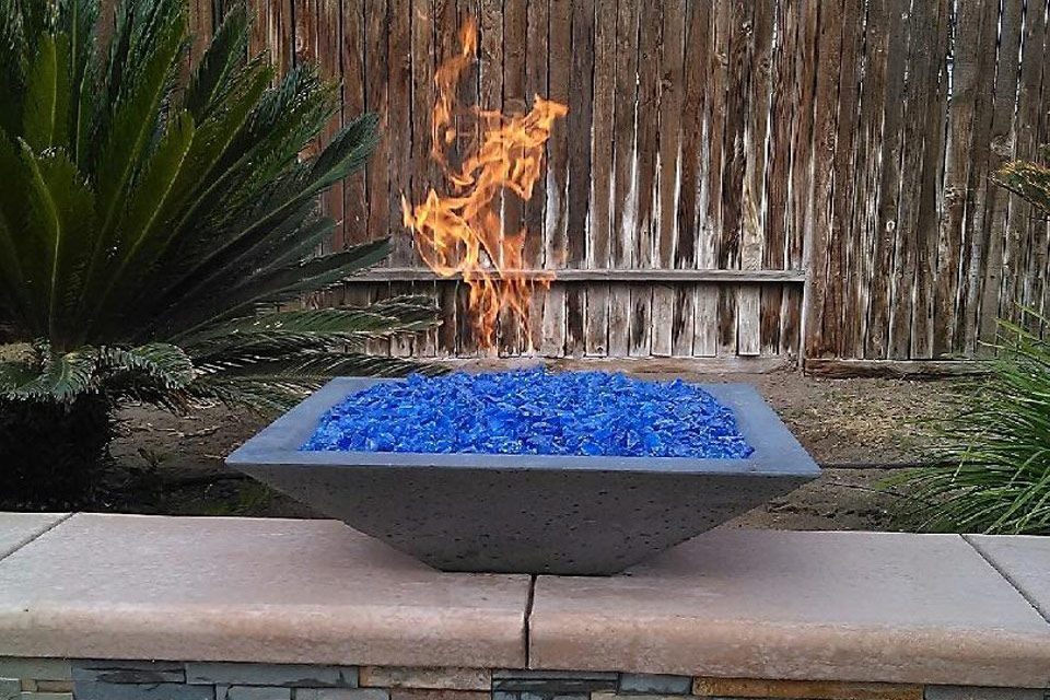 Lit fire bowl with blue stones next to a swimming pool.