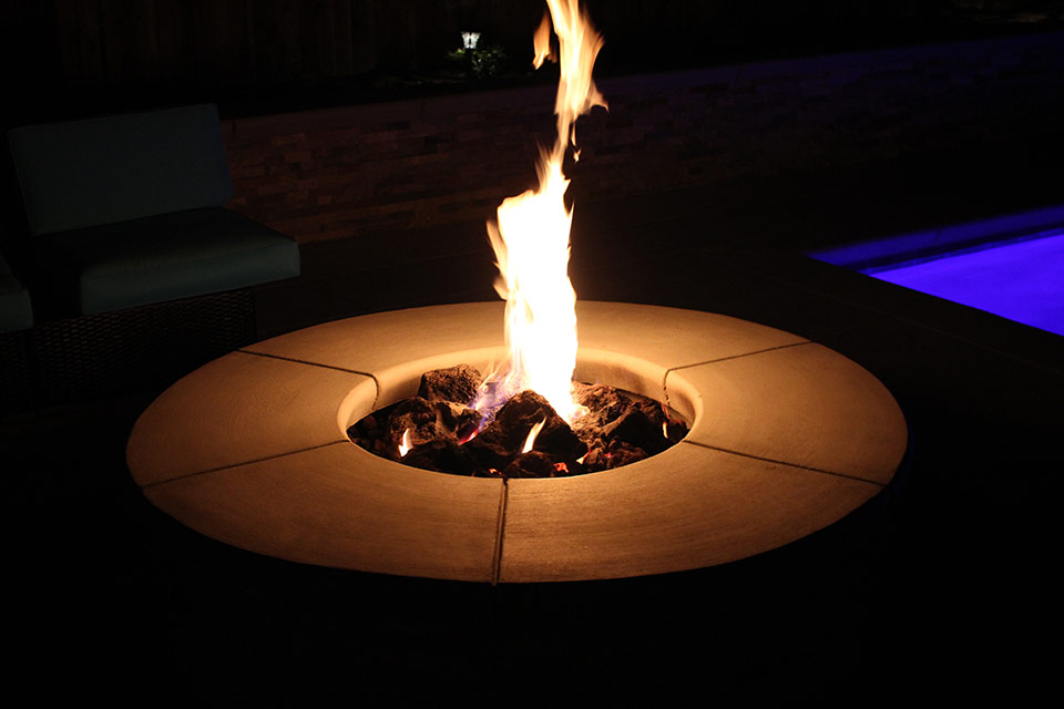 Flames billow from a poolside fire pit at night in Bakersfield, California.