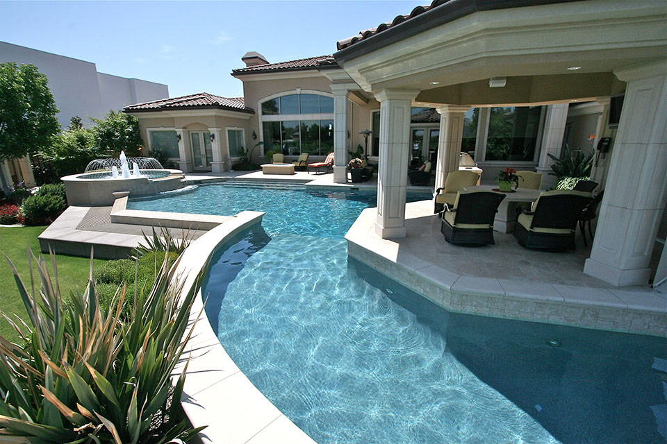 Beautiful outdoor living area with a fire pit, a fountain and wrapped by a swimming pool. By Paradise Pools & Spas.