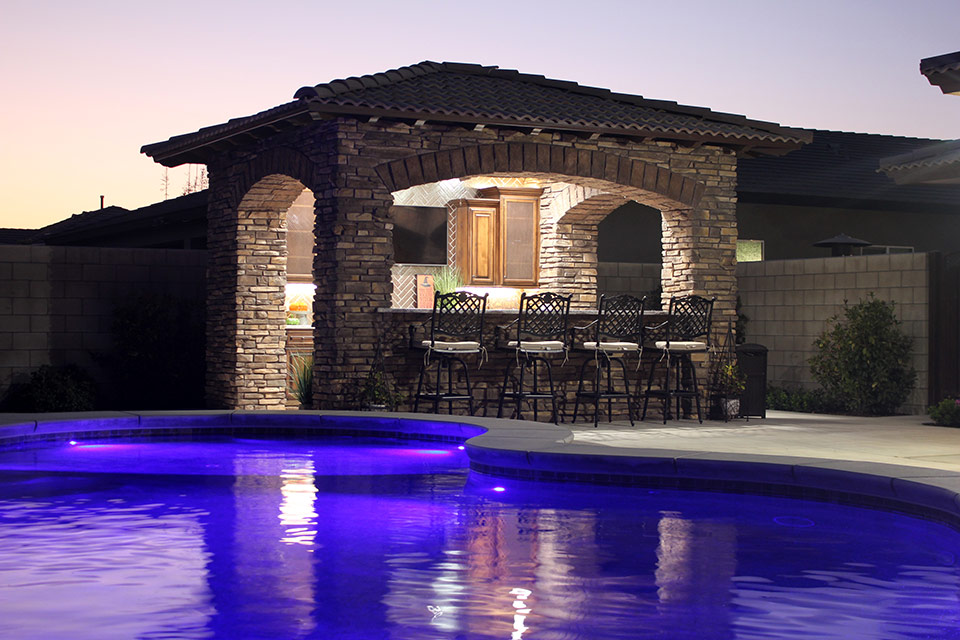 Outdoor poolside bar with seating next to a swimming pool at dusk, in Bakersfield.