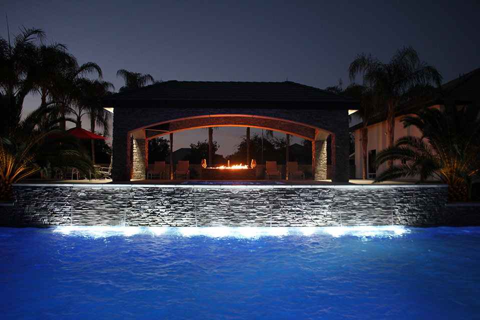Evening time poolside by a fire pit that is part of a Paradise Pool & Spas build outdoor living space.