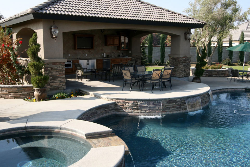 A beautiful outdoor living space with a covered kitchen, multiple dining areas, a pool and a spa.  By Paradise pools & Spas.