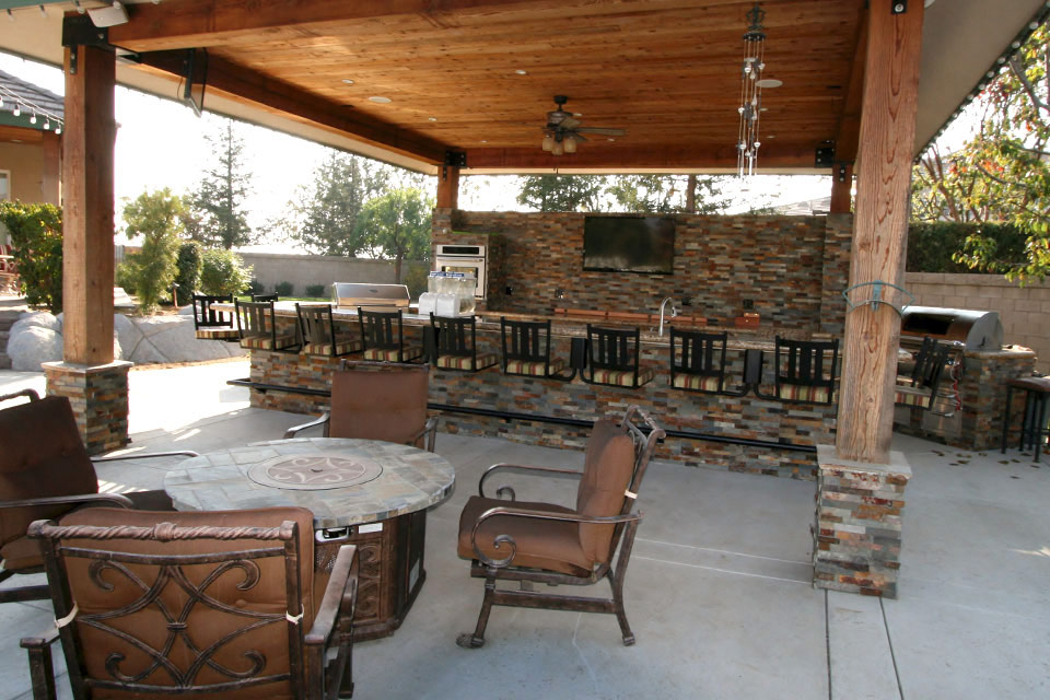 Covered outdoor bar with seating for 12 at the bar. Grill, television and additional seating.