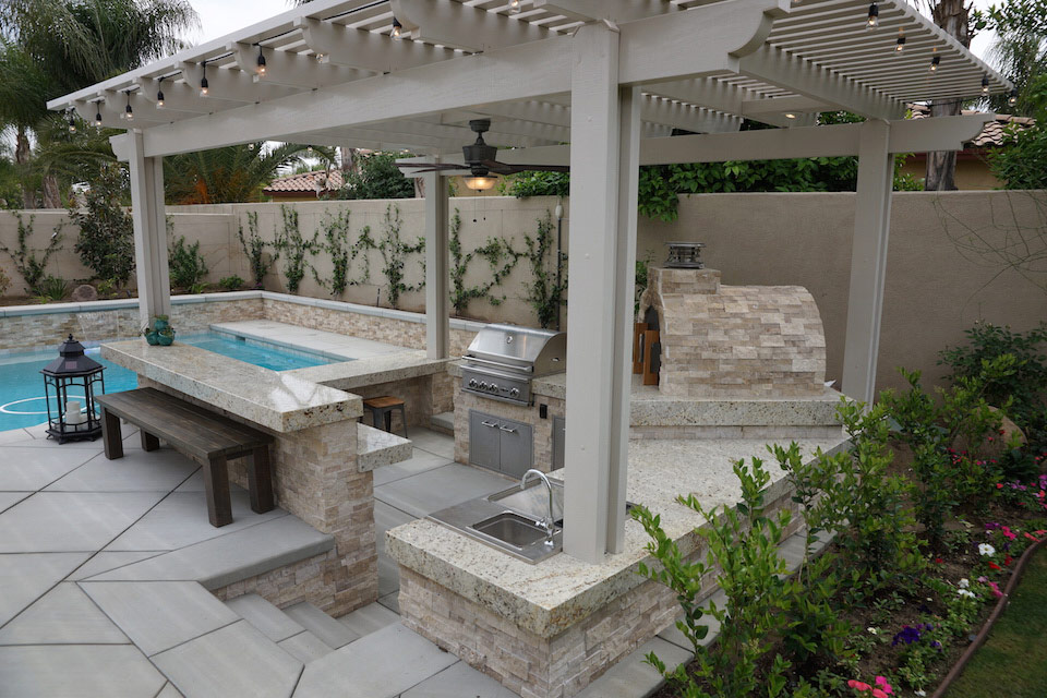 Outdoor living space with bar, grill, sink and pizza overn.