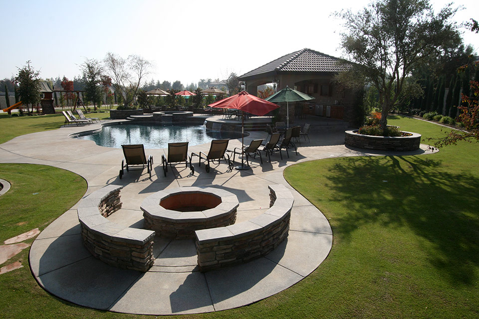 Outdoor living space with kitchen, pool, spa, fire pit and multiple covered and uncovered seating areas. Bakersfield, CA.