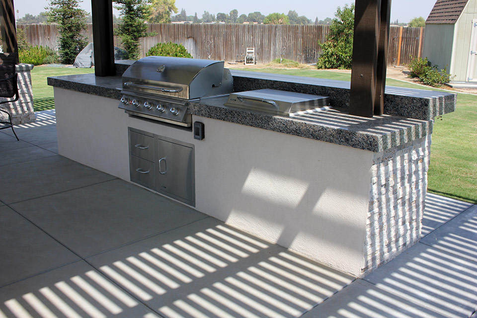 Covered outdoor kitchen with grill.