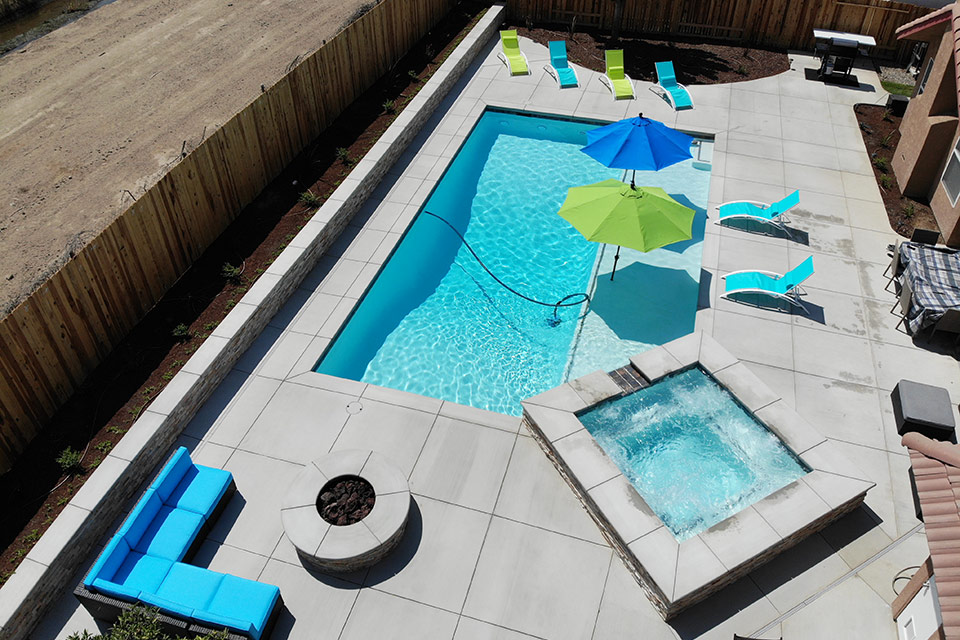 Aerial view of outdoor living area with pool, spa, fire pit and colored umbrellas.
