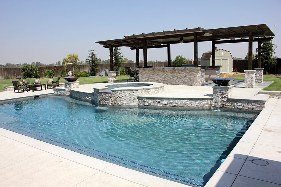 Outdoor kitchen next to a beautiful pool with raised deck, spa, fire bowls and water features.