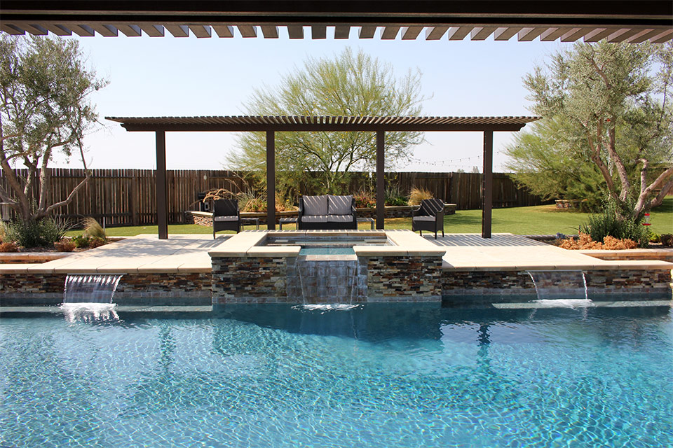 Outdoor covered seating area next to pool and spa with water features.
