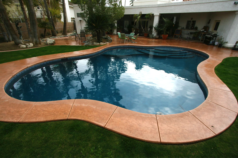 Custom pool with colored concrete decking in a Bakersfield backyard.