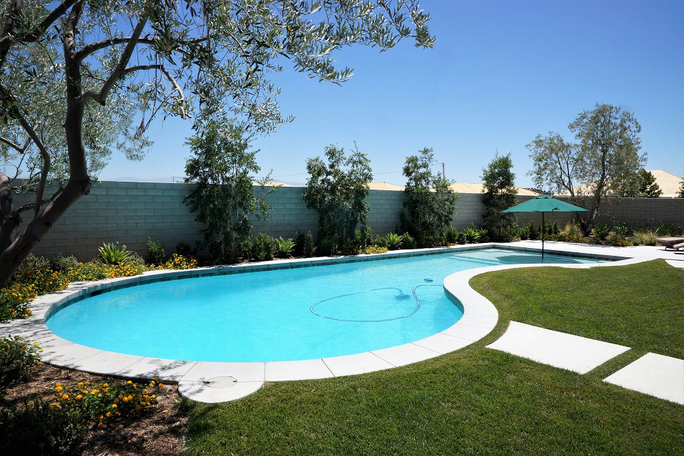 Custom swimming pool with green umbrella in Bakersfield, CA.
