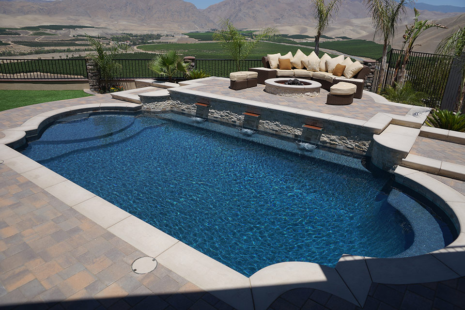Greacian Swimming Pool with Raised Deck, 3 waterfalls and a fire pit with mountains in the background.