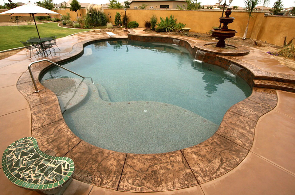 Custom Bakersfield swimming pool with raise deck, fountain and other water features.