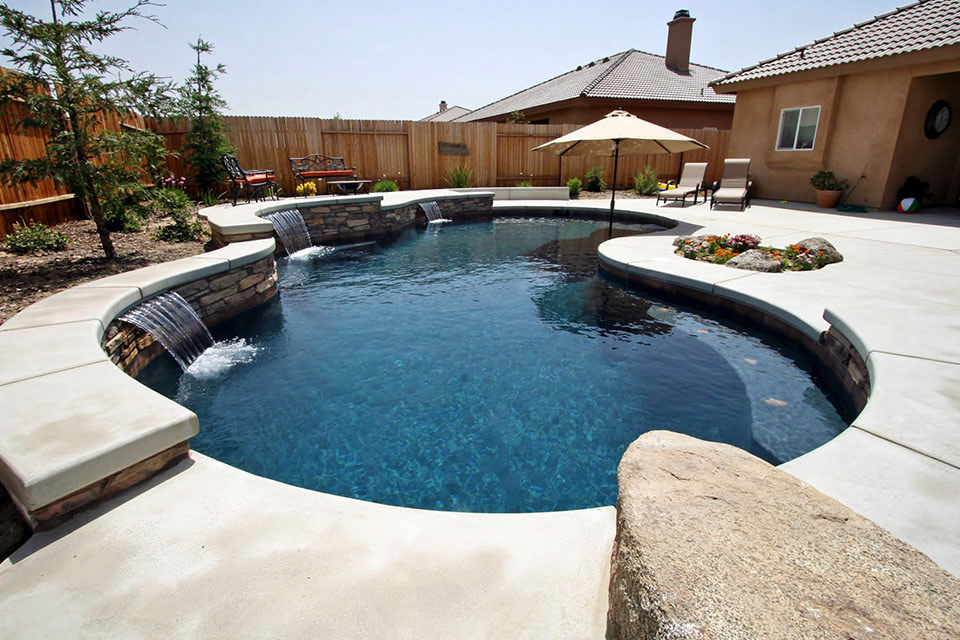 Custom swimming pool with raised deck, water features and an umbrella.