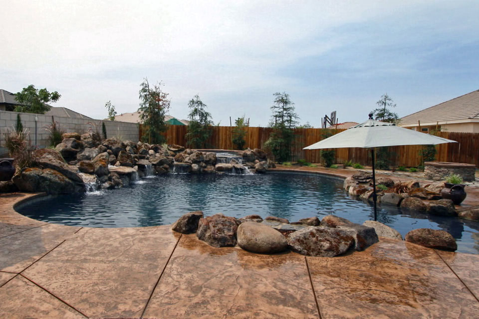 Paradise Pools & Spas built pool with water falls and natural stone.