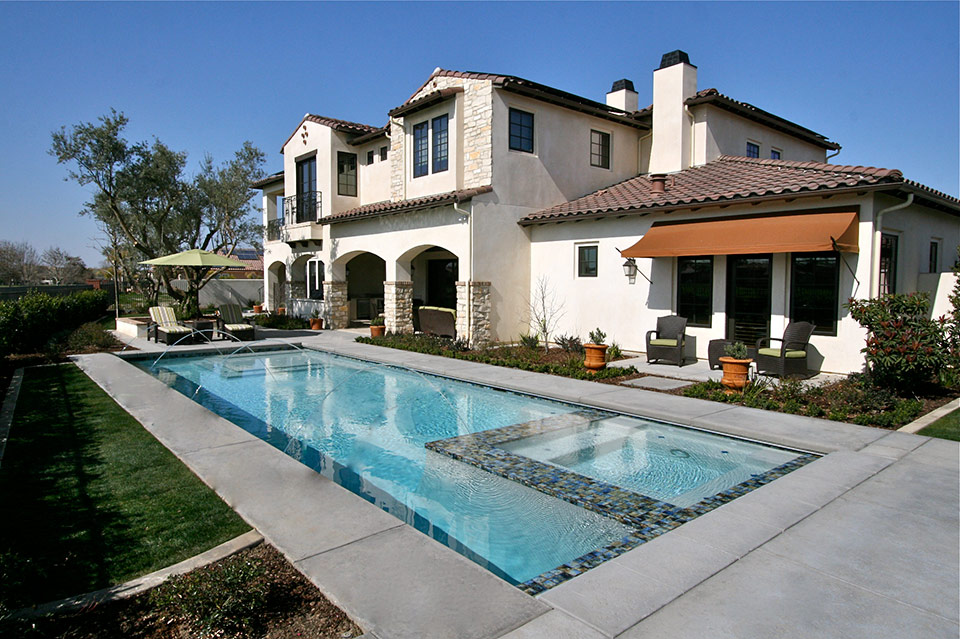Geometric pool with in-pool spa in green California backyard.