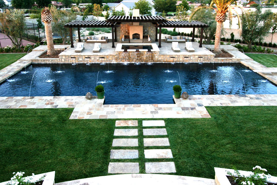 Large custom swimming pool with raised deck, spa, fireplace and multiple water features. Built by Paradise Pools & Spas.