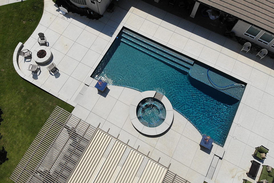 Aerial view of custom pool with circular spa, fire bowls, fire pit and water features.