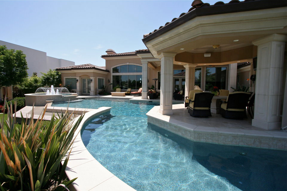 Exquisite swimming pool that wraps around a a beautiful outdoor living space with a custom fountain.