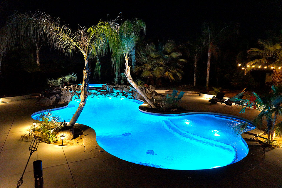 Nighttime shot of a beautifully lit pool with palm trees, custom spa and rock waterfall in Bakersfield, CA.l