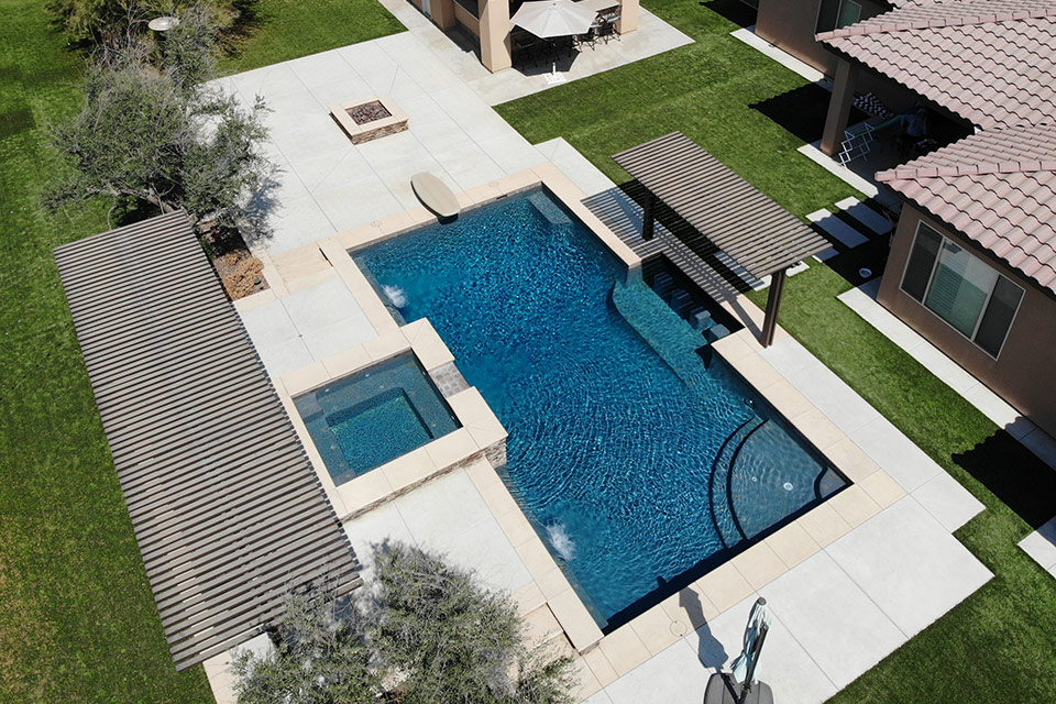 Aerial view of a geometric swimming pool and spa with fire pit, diving board and in pool seating.