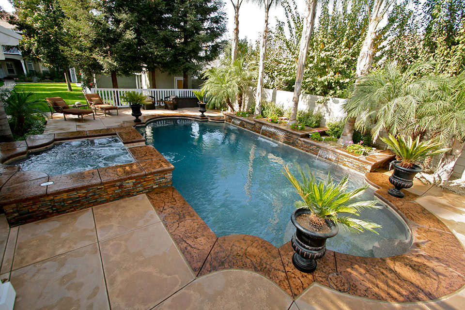 Grecian style pool with raised deck, Grecian style spa, and several water features.