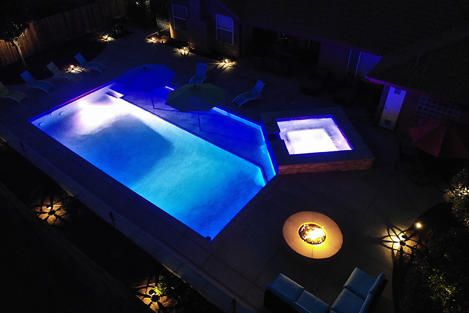 Nighttime aerial view of a lit swimming pool and spa, next to a blazing fire pit.