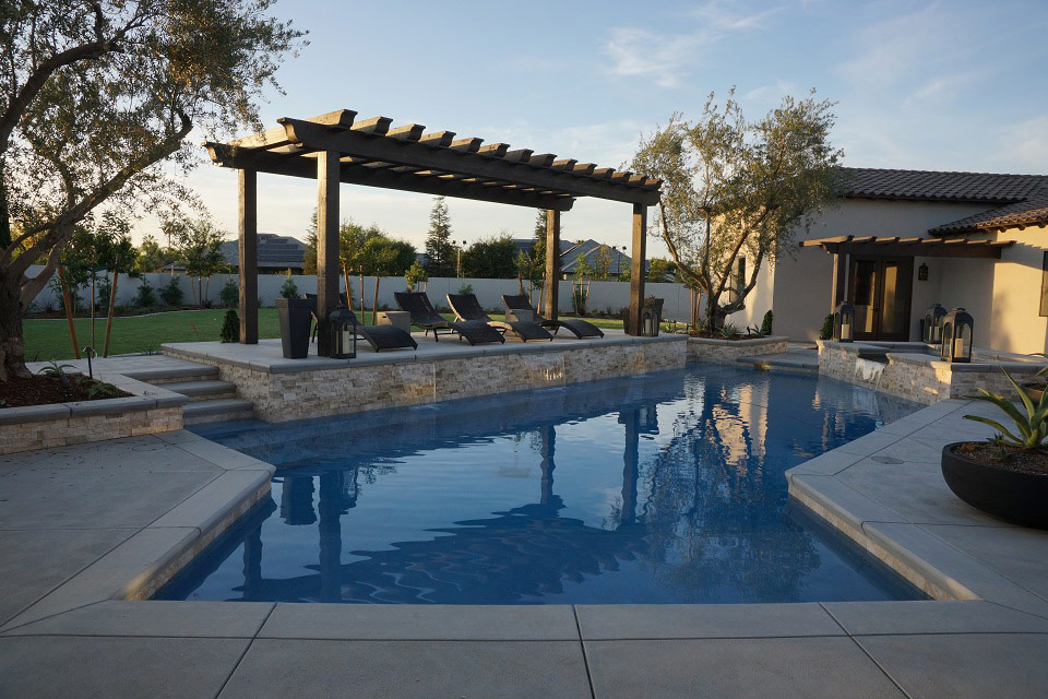 Custom swimming pool with multiple water features, a stairway into the pool, outdoor lounging area, and a spa.