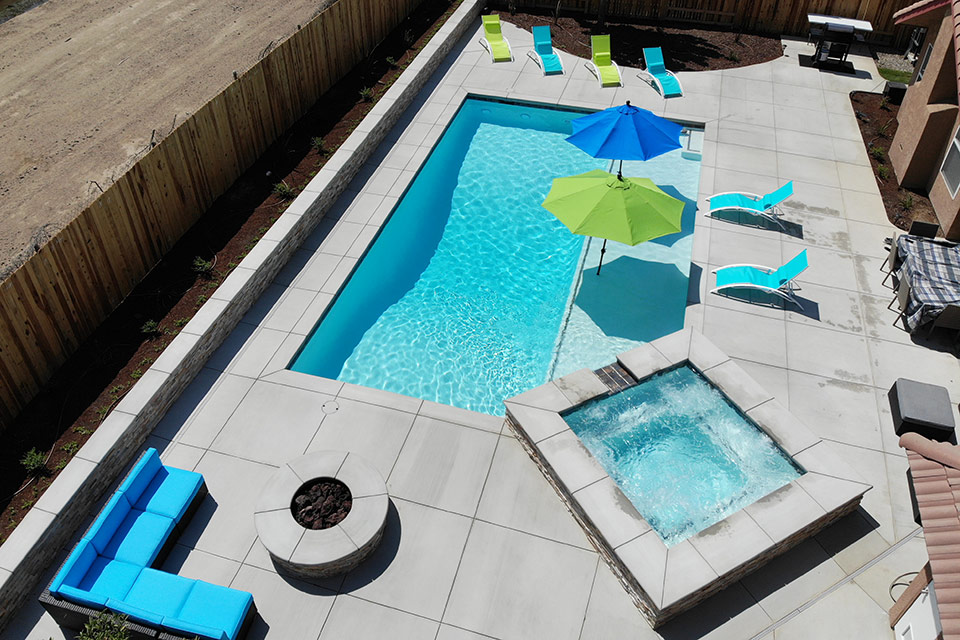 Aerial view of geometric pool and spa with blue and green umbrellas and matching lounge chairs in Bakersfield.