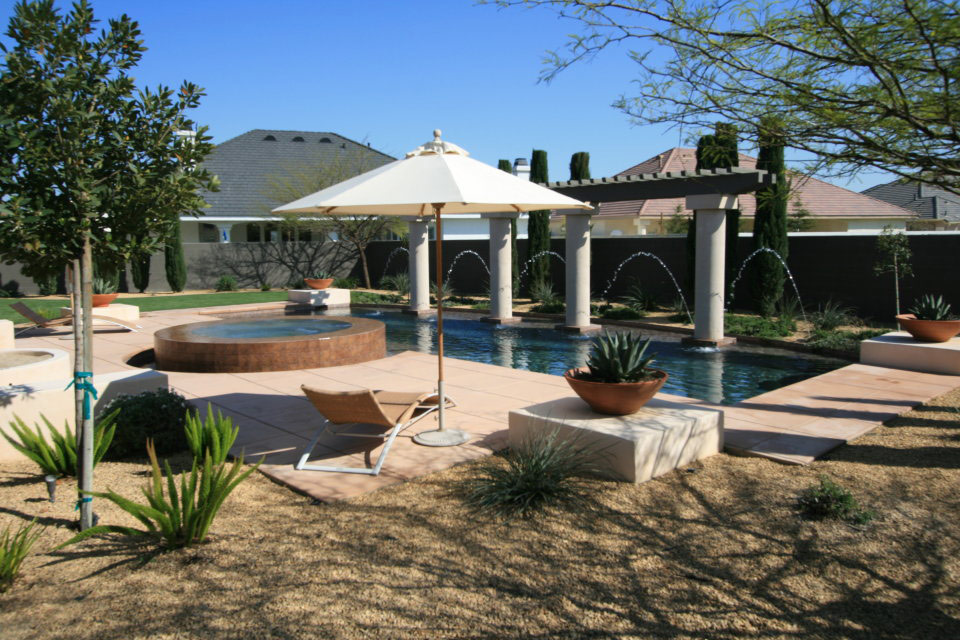 Custom swimming pool and spa with columns and water features.