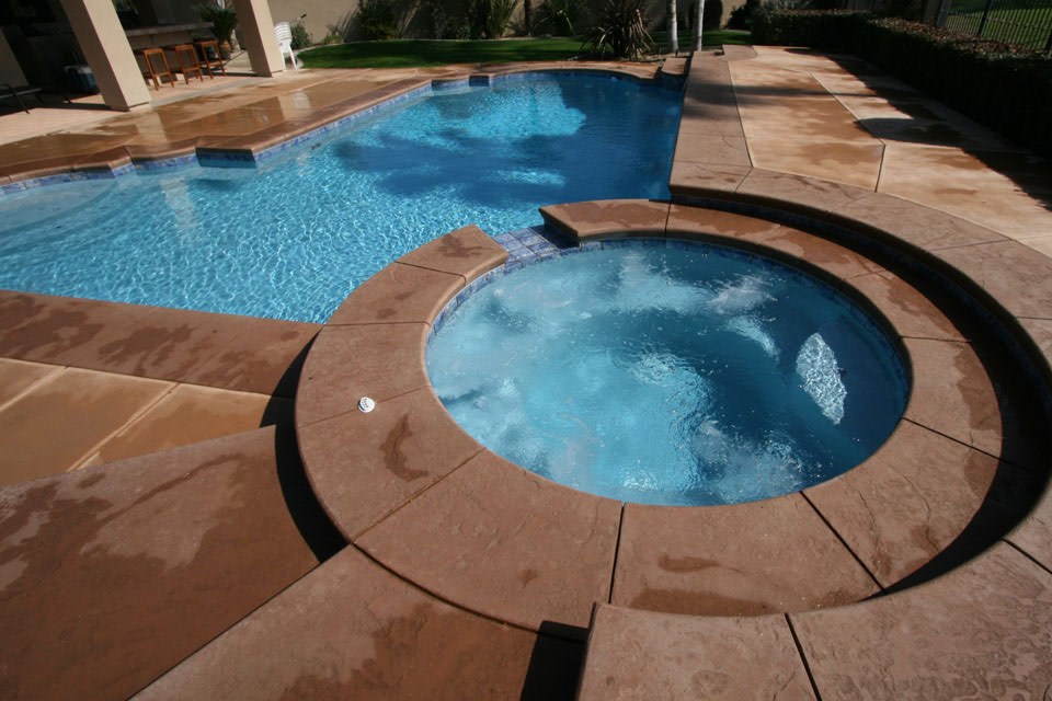 Circular spa with a Grecian style pool with raised deck.