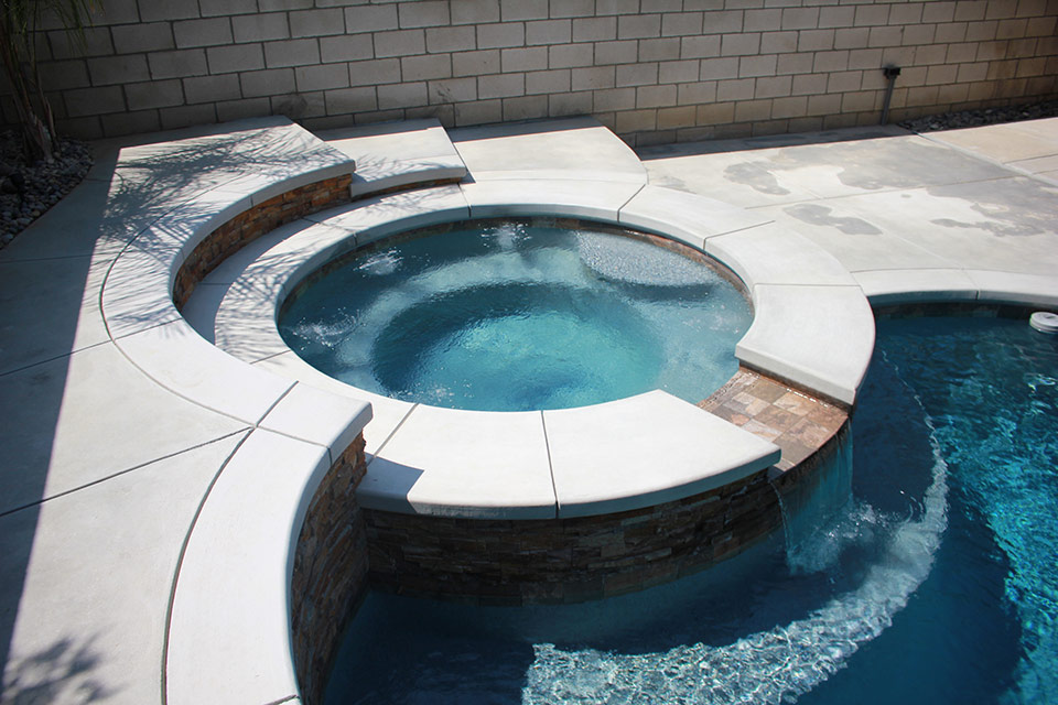Circular spa with raised deck and a waterfall.