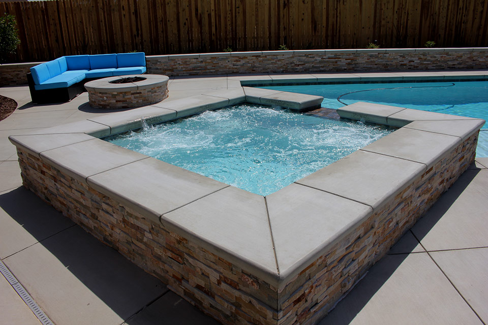 Square spa with water feature next to a fire pit built by Paradise pools & Spas.