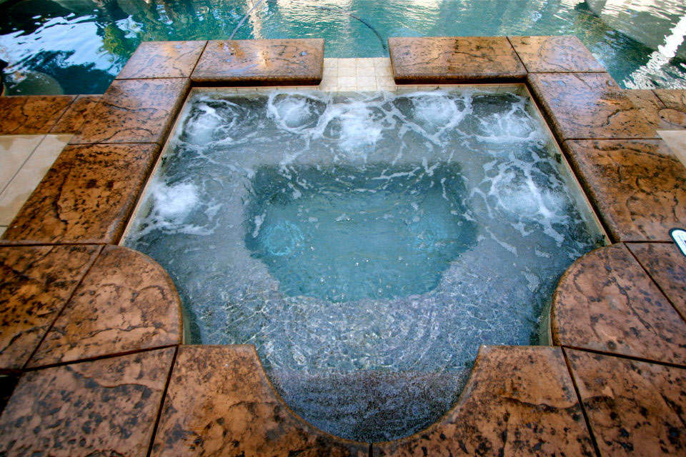 Custom Spa with Grecian style next to a swimming pool.