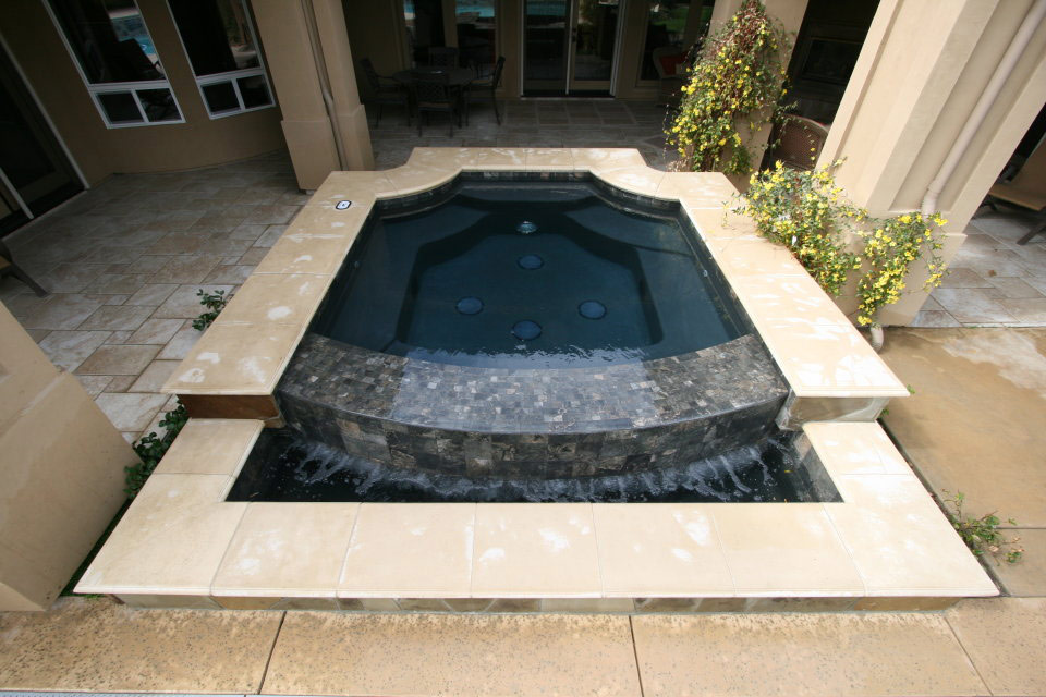 Grecian style spa with built in negative edge waterfall in Bakersfield.