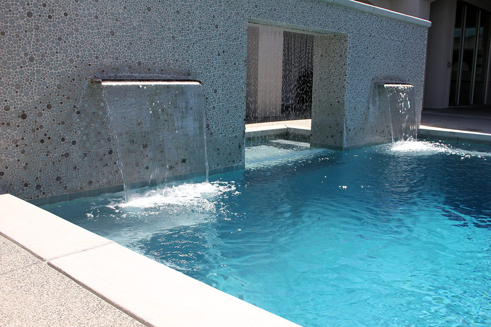 A large water wall featuring two scuppers and a rain curtain pours into a Bakersfield pool.
