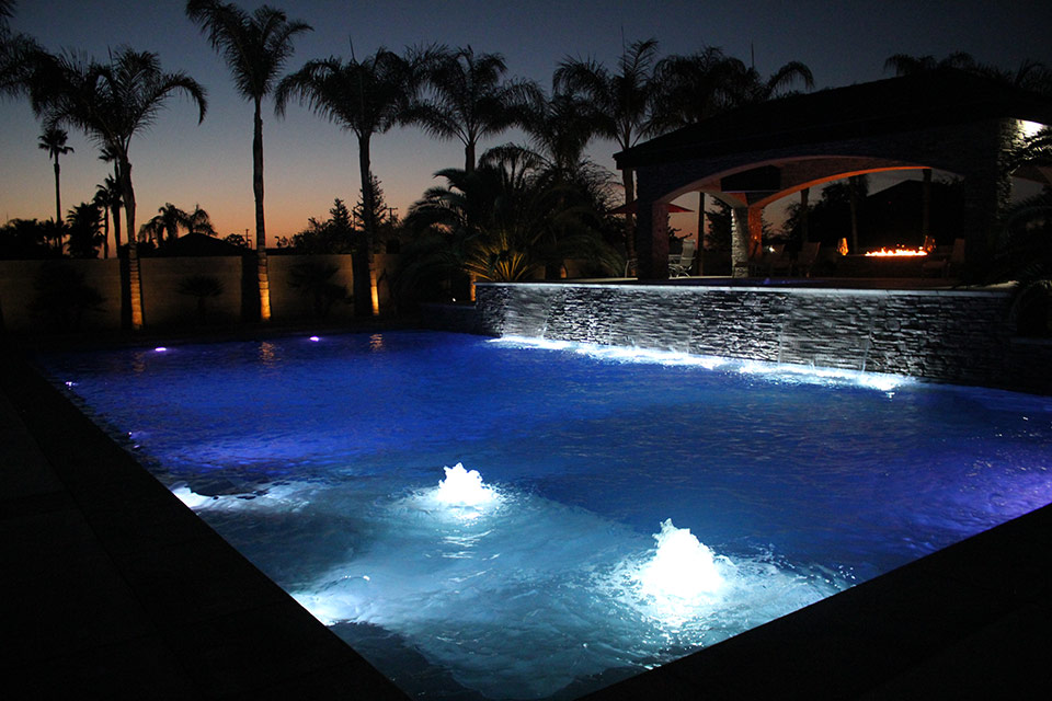 Three scuppers and two bubblers are lit up in this evening view of a beautiful Bakersfield swimming pool.