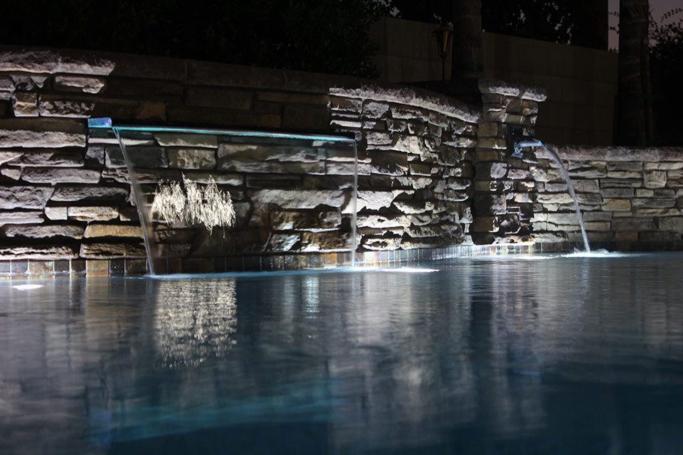 Two styles of scuppers pour into this swimming pool at night.