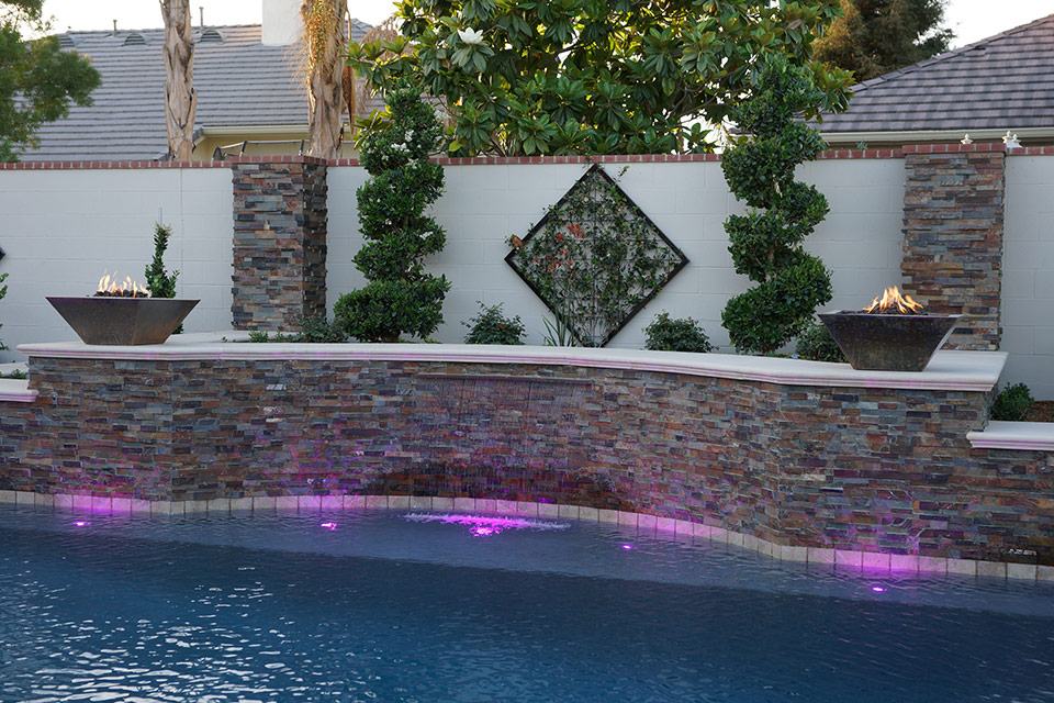 A scupper pours into a pool lit by magenta lights.