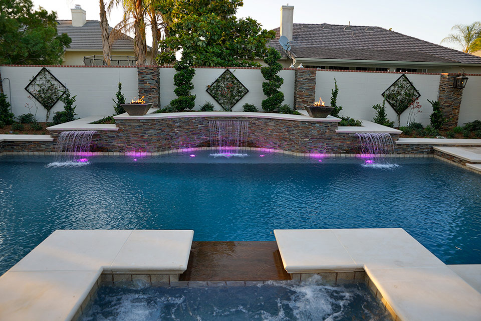 Three scuppers pour into this pool lit with colored lighting.