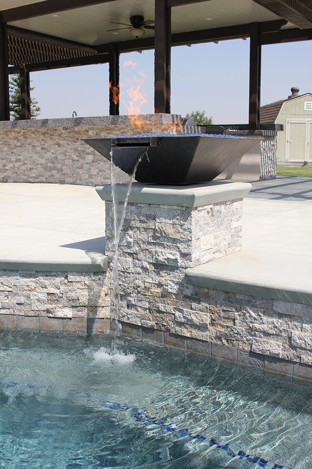 Fire bowl sconce pours into a Bakersfield pool.