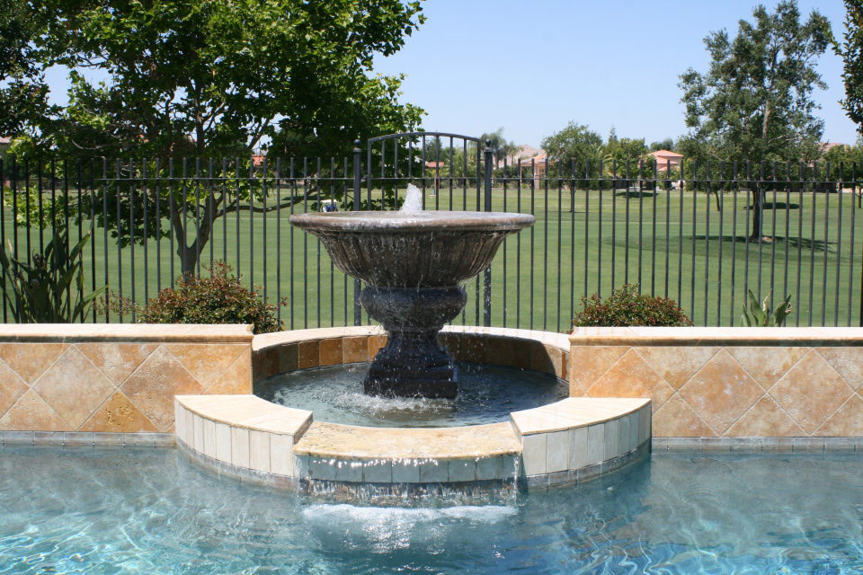 Fountain with a spillover with golf course in background.