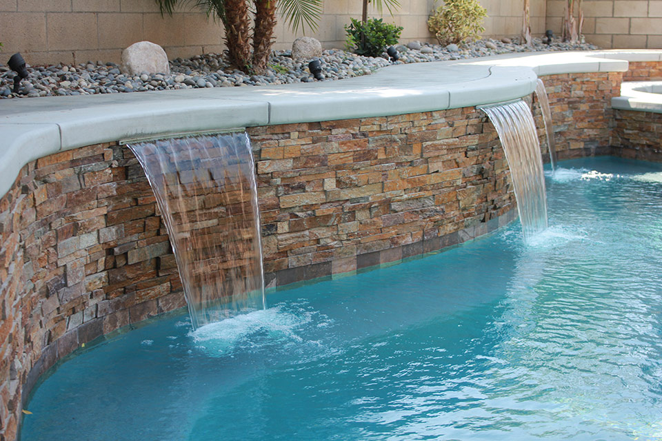 Three scuppers pour into a aqua blue swimming pool.