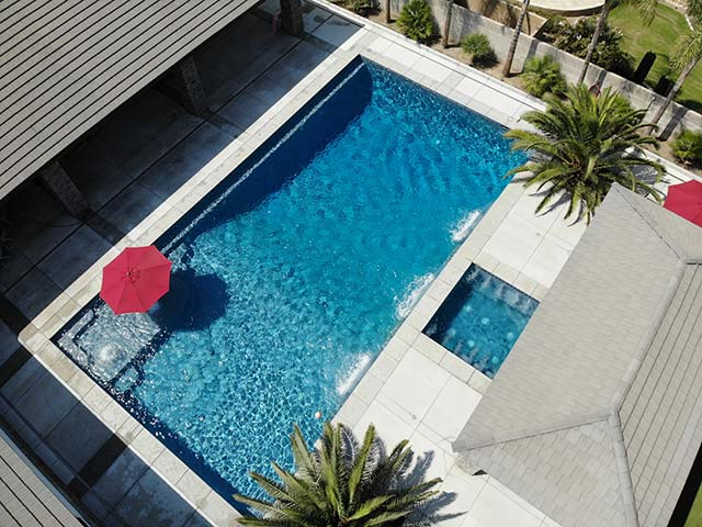 Aerial view of a beautiful Bakersfield pool and spa, accented by a large red umbrella.