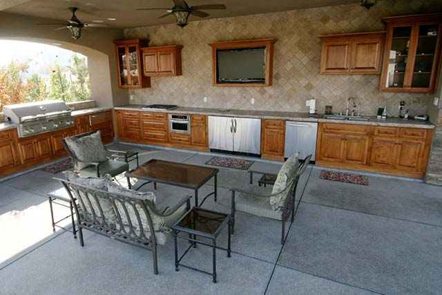 Beautiful Outdoor Living Space with kitchen, barbecue grill, television, seating, refrigerator and counter space.
